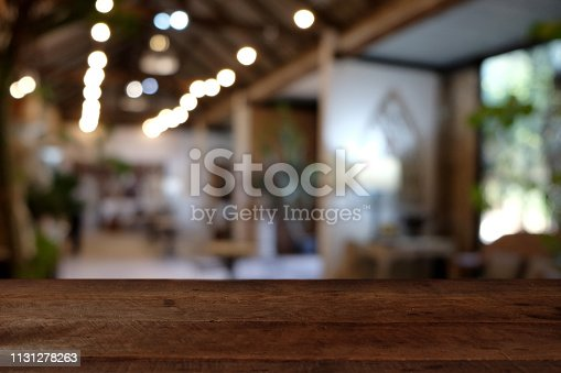 924418708istockphoto wood table on blur of cafe, coffee shop, bar, resturant, background - can used for display or montage your products 1131278263