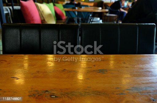924418708istockphoto wood table on blur of cafe, coffee shop, bar, resturant, background - can used for display or montage your products 1133748801
