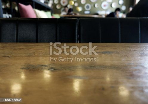 924418708istockphoto wood table on blur of cafe, coffee shop, bar, resturant, background - can used for display or montage your products 1133748802