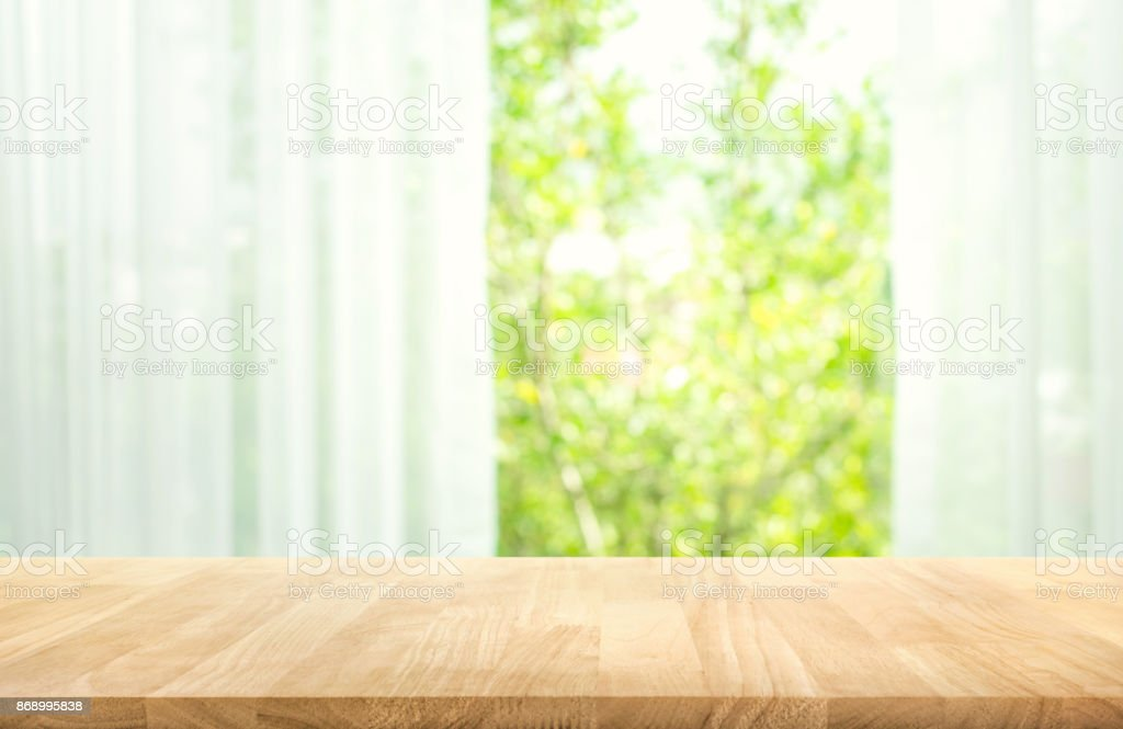 Wood table on blur of curtain with window view garden