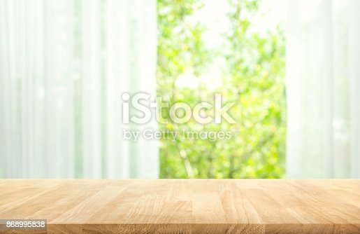 885452818istockphoto Wood table on blur of curtain with window view garden 868995838
