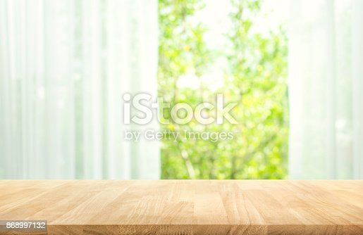 885452818istockphoto Wood table on blur of curtain with window view garden 868997132