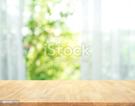 885452818istockphoto Wood table on blur of curtain with window view garden 884082712