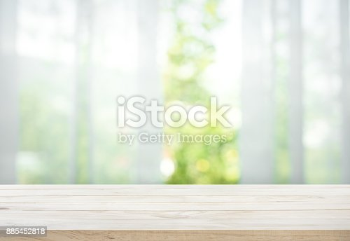 885452818istockphoto Wood table on blur of curtain with window view garden 885452818