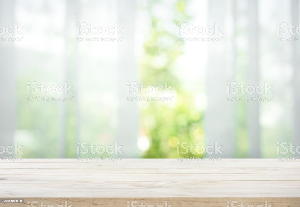 Wood table on blur of curtain with window view garden stock photo