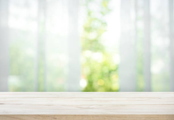 wood table on blur of curtain with window view garden - surface level stock photos and pictures