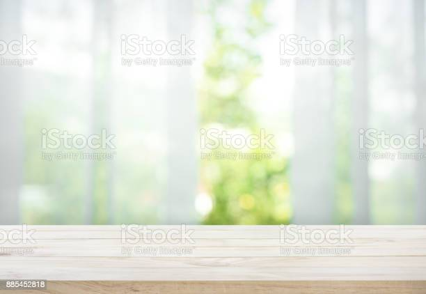 Photo of Wood table on blur of curtain with window view garden