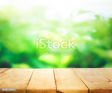680878382istockphoto Wood table on blur of fresh green garden with sunlight 849025532