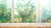 Wood table on blur of window with garden flower background