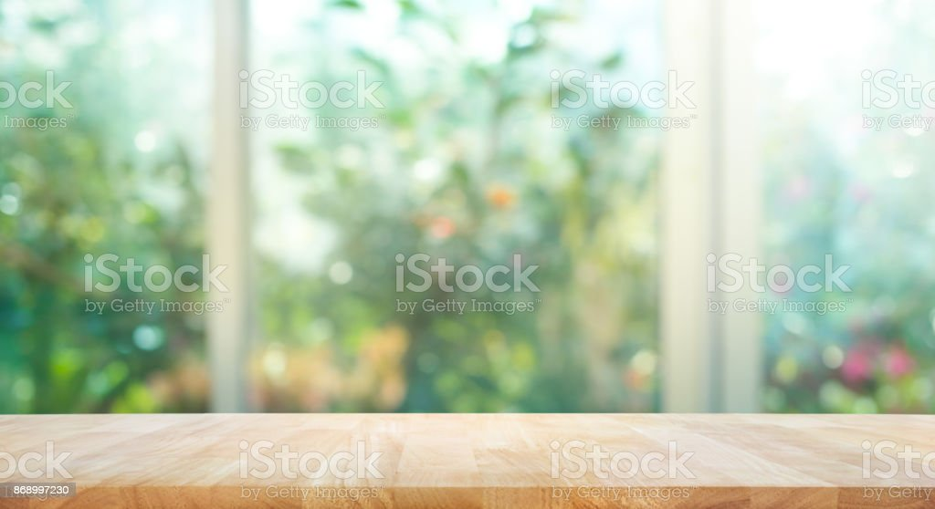 Wood table on blur of window with garden flower background stock photo