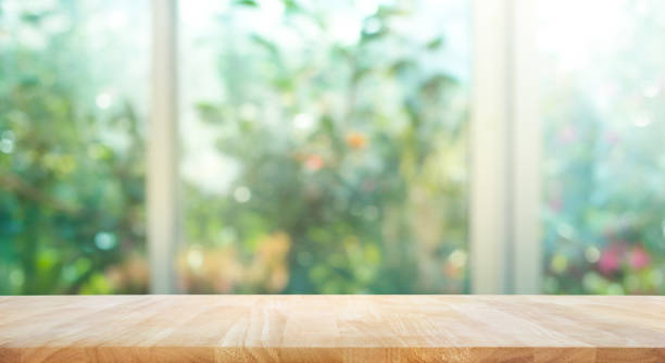 wood table on blur of window with garden flower background - house with flowers stock photos and pictures