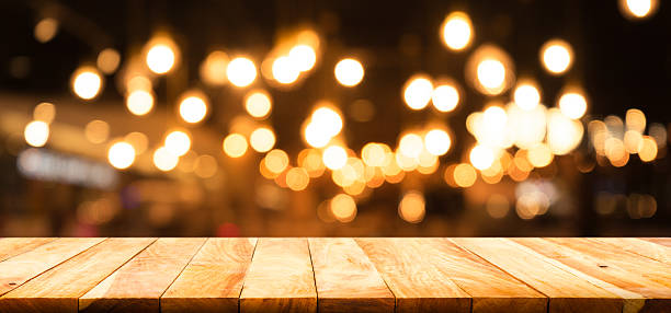 wood table on blurred cafe restaurant with light background - goldene bar stock-fotos und bilder