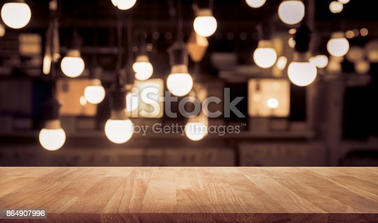 864907996istockphoto Wood table on blurred counter bar cafe shop with light 864907996
