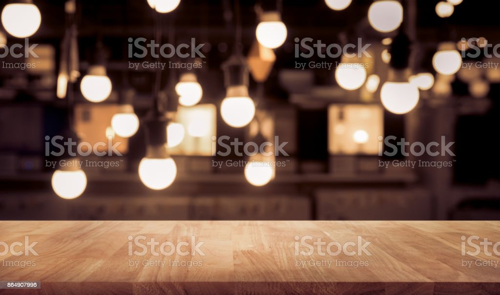 Wood table on blurred counter bar cafe shop with light stock photo