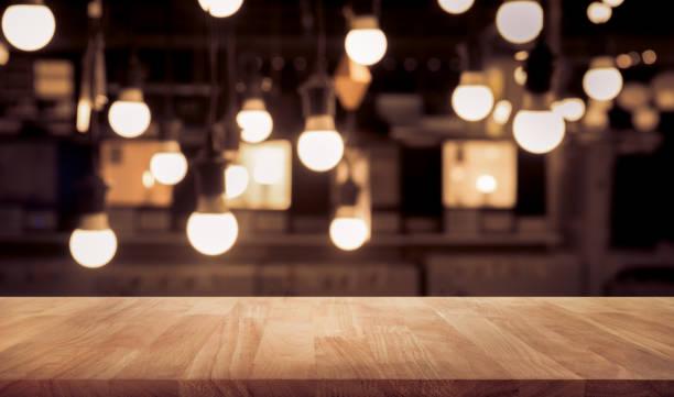 holztisch auf unscharfen theke bar café shop mit licht - tresentisch stock-fotos und bilder