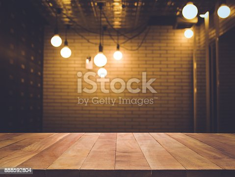 864907996istockphoto Wood table on blurred counter bar cafe shop with light 888592804