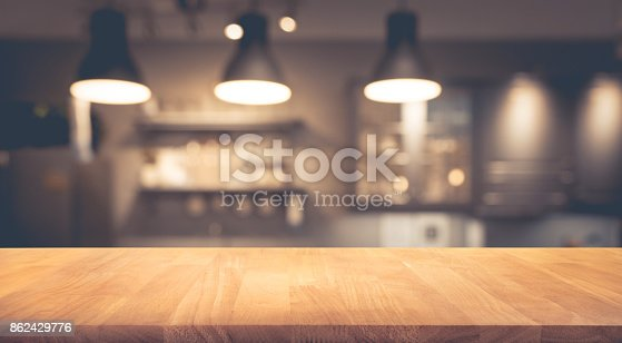 862429776 istock photo Wood table on blurred of counter cafe with light bulb 862429776