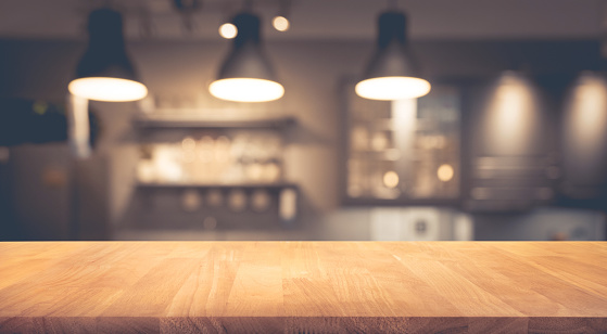 Wood table on blurred of counter cafe with light bulb