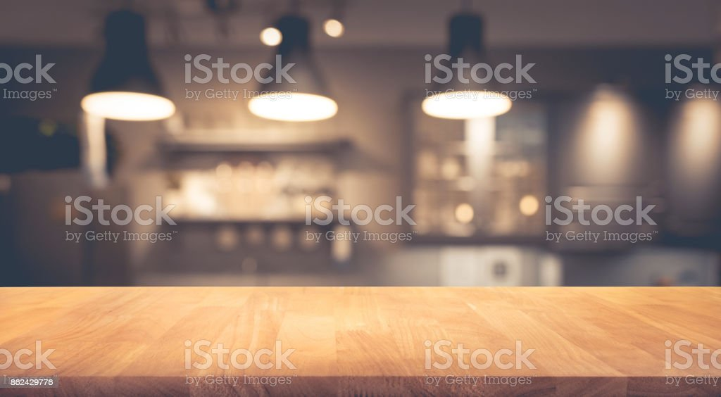 Wood table on blurred of counter cafe with light bulb - foto stock
