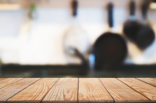 593305530 istock photo wood table over blurred kitchen background 1129810822