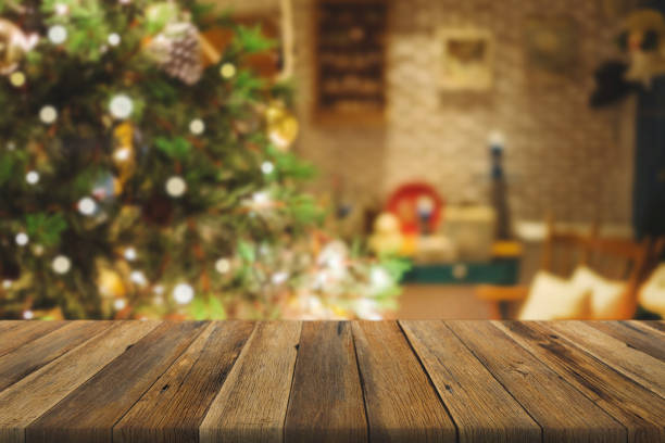 wood table over christmas tree with decoration blur background. can be used for display or montage products. - christmas table foto e immagini stock