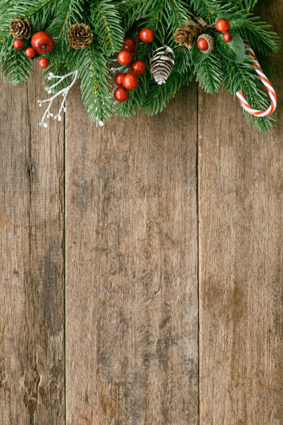 wood table plank in vertical with pine leaves and pine cones, holly balls and candy cane in christmas theme concept. wooden background in top view flat lay with copy space for christmas wallpaper. - vacations food stock pictures, royalty-free photos & images