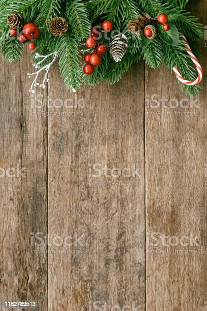 Photo of Wood table plank in vertical with pine leaves and pine cones, holly balls and candy cane in Christmas theme concept. Wooden background in top view flat lay with copy space for Christmas wallpaper.