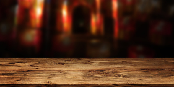 Empty wood table surface in front of red gloomy vault with short depth of field for a halloween background