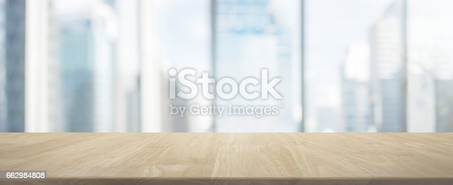 istock Wood table top and blur glass window wall building banner background 662984808