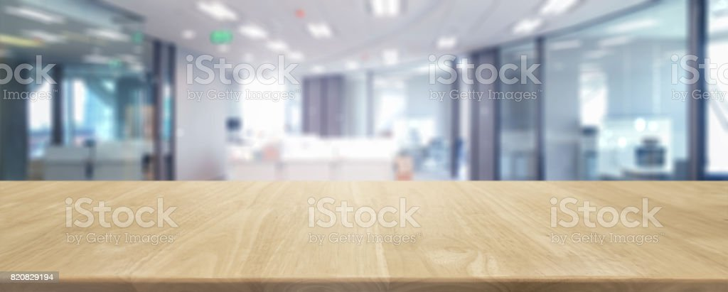 Wood table top and blurred bokeh office interior space background -...