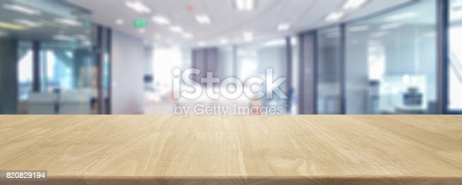 istock Wood table top and blurred bokeh office interior space background - can used for display or montage your products. 820829194