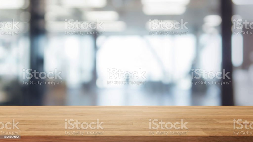 Wood table top and blurred bokeh office interior space background - can used for display or montage your products. stock photo
