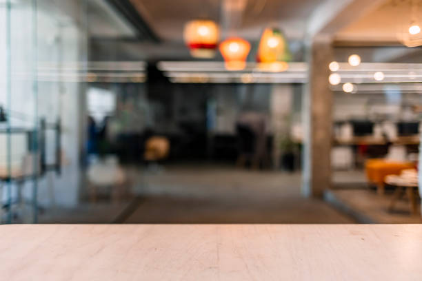 wood table top and blurred bokeh office interior space background - banchi scuola foto e immagini stock