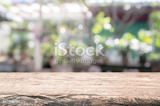647209792 istock photo Wood table top and blurred restaurant exterior background. 647209792