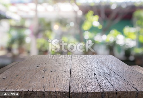 647209792 istock photo Wood table top and blurred restaurant exterior background. 647209804