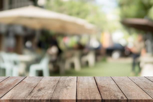 tabela de madeira superior e turva restaurante exterior plano de fundo. - festa no jardim - fotografias e filmes do acervo