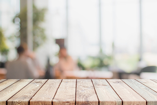 Wood table top and blurred restaurant interior background
