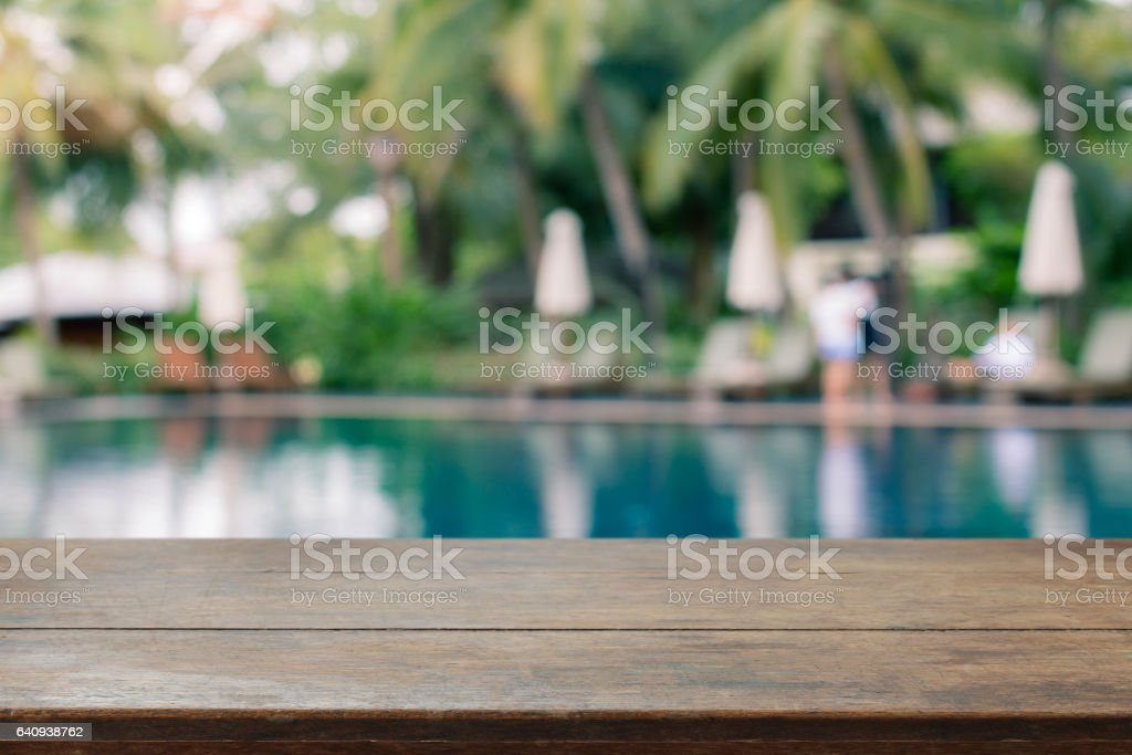 Wood table top and blurred swimming pool background. - can used for display or montage your products. stock photo