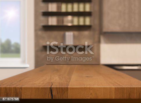 istock Wood table top as kitchen island on blur kitchen background - can be used for display or montage your products 871675768