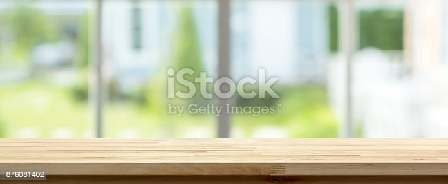 istock Wood table top inside the house with blur green garden outside window in background, panoramic banner 876081402