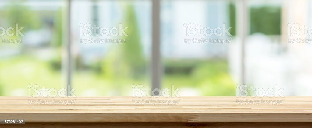 Wood table top inside the house with blur green garden outside window in background, panoramic banner stock photo