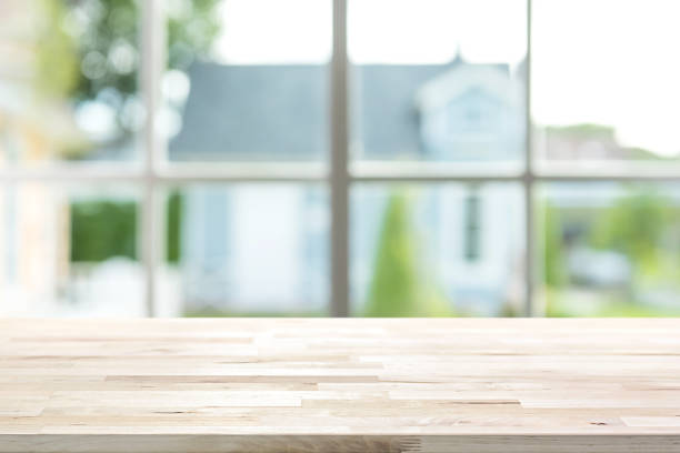 Wood table top inside the house with blur green garden outside window in background stock photo