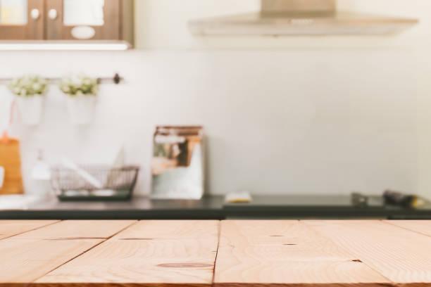 top insel holztisch mit moderner küche zimmer innen hintergrund weichzeichnen - wärmeplatte stock-fotos und bilder
