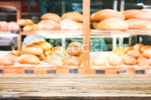886308526 istock photo Wood table top on bakery shop background. 890011222