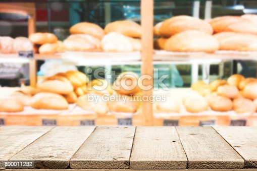 886308526 istock photo Wood table top on bakery shop background. 890011232