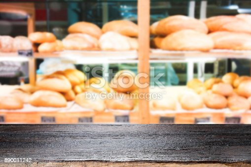 886308526 istock photo Wood table top on bakery shop background. 890011242