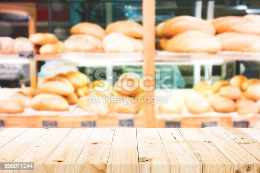 886308526 istock photo Wood table top on bakery shop background. 890011244