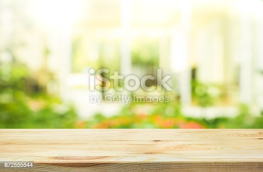 680878382 istock photo Wood table top on blur abstract green from garden background. 672555544