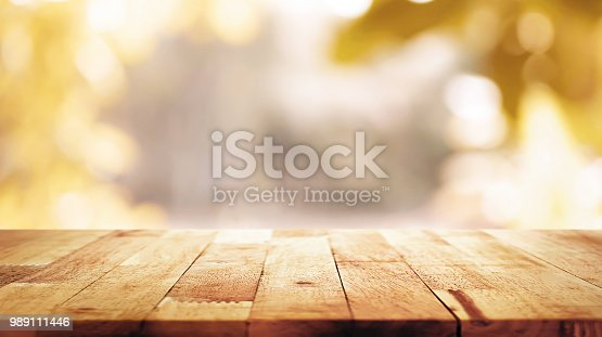 istock Wood table top on blur abstract natural foliage bokeh background, vintage tone 989111446