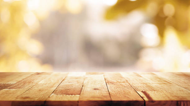 wood table top on blur abstract natural foliage bokeh background, vintage tone - осень стоковые фото и изображения